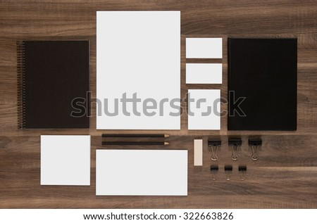 Set of branding mockup on brown wooden desk. Blank business cards with documents, paperclips and black notepads. - stock photo