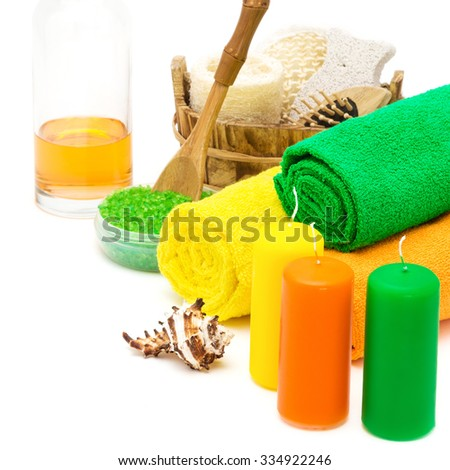Set of bright spa accessories in green, orange, yellow colors on white background. Towels, candles, shell, sea salt, shower gel and wooden basket with loofah, massage comb, pumice, body scrubber - stock photo