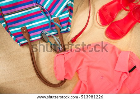 set of bright summer clothes for the beach on the golden sand
