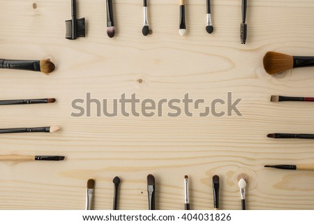 set of brushes for makeup scattered chaotically on wooden background