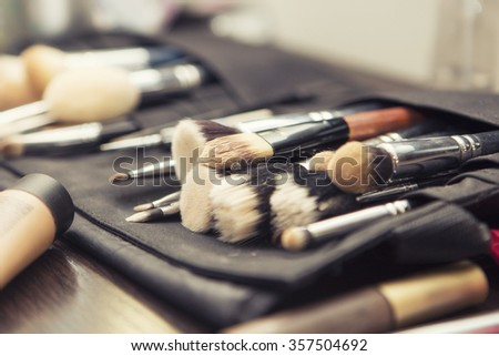 Set of brushes (make up application tools) laying on a table randomly - stock photo