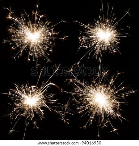 Set of burning christmas sparkler isolated on black background - stock photo