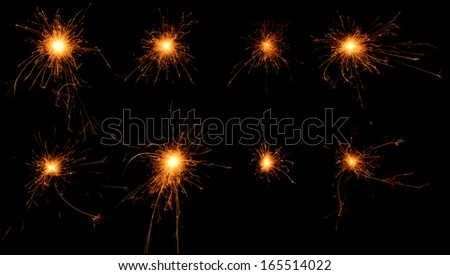Set of burning sparklers isolated on black background. Small fireworks giving off sparks of fire. Sparks explosion. - stock photo