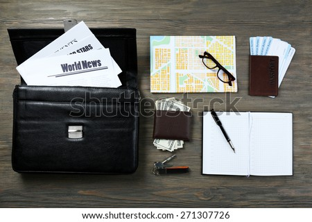 Set of business trip stuff on wooden background - stock photo