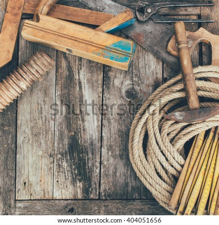 Set of carpenter tools on wood panel background with copy space - stock photo