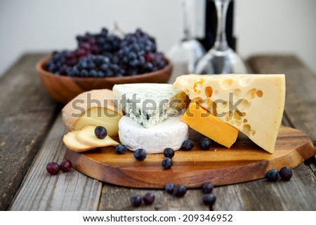 Set of cheeses with a bottle of red wine and dark grapes in the background, selective focus - stock photo