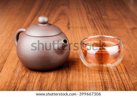 Set of chinese porcelain teapot and glass cup with tea on wooden texture desk - stock photo