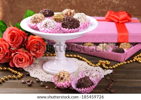 Set of chocolate candies on table on brown background - stock photo