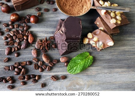 Set of chocolate with nuts, herbs and coffee beans on wooden table, closeup - stock photo