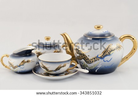 Set of coffee. Cup, sugar bowl, milk jug and coffee pot. Blue-eyed, golden dragon pattern. - stock photo