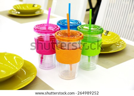Set of colored, plastic utensils and cups with straw - stock photo