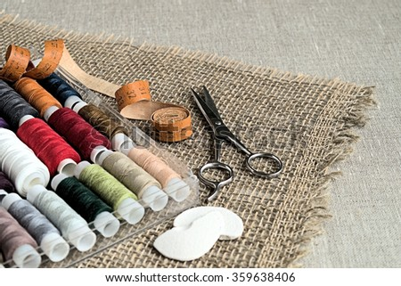 Set of  colored sewing thread, scissors and measuring tape on a napkin of burlap.