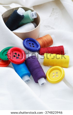 Set of colored thread and buttons on white textile