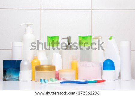 set of colorful cosmetic bottles over white tiled wall in bathroom