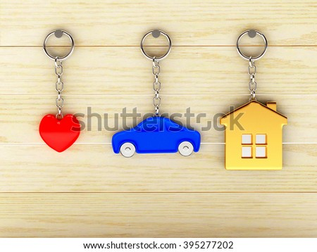 Set of colorful keychains in the form of the house, car and heart is hanging on the wooden wall  - stock photo