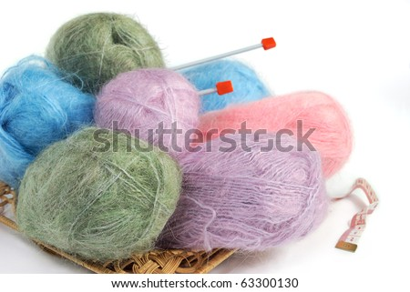 set of colorful knitting yarn with spokes in a basket - stock photo