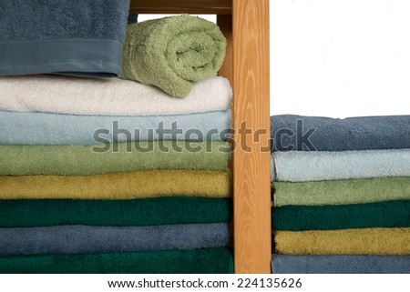 Set of colorful towels on wooden shelf, isolated on white background - stock photo