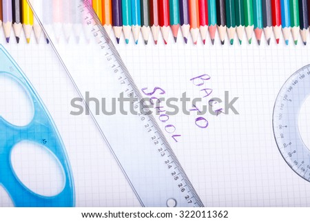 Set of colorful wooden pencils yellow green red pink orange blue and brown lying in row on table with white paper sheet with back to school text and ruler, horizontal picture - stock photo
