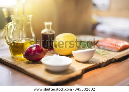 Set of condiments with a lemon, red onion, olive oil, sea salt and vinegar for a fresh salmon lying on the cutting board and wooden table - stock photo