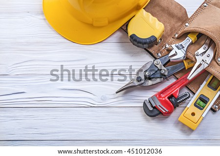 Set of construction tooling in tool belt hard hat on wooden board.