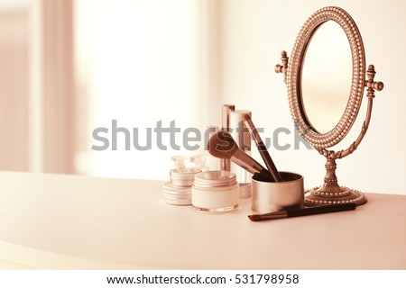 Set of cosmetics and vintage mirror on white table against light background