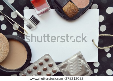 set of cosmetics, contraceptives, blank sheet of paper