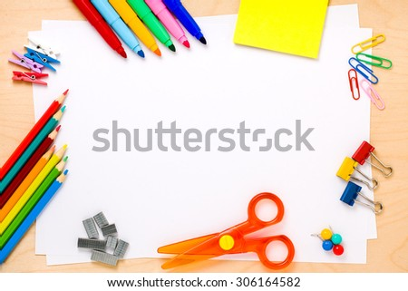 Set of crayons, scissor, colored clips, pushpins, pegs, post-its, felt-tip colored pens and other supplies arranged to make a frame around white blank sheets - stock photo