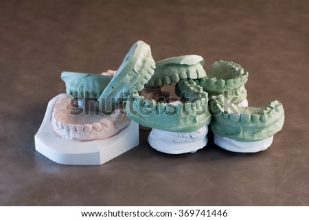 set of dentures. False teeth on brown background - stock photo