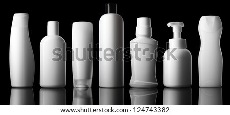 Set of different bottles for beauty, hygiene and health on a black background with reflection, they shampoo, conditioner and other hair products, each of them shot on separately. - stock photo