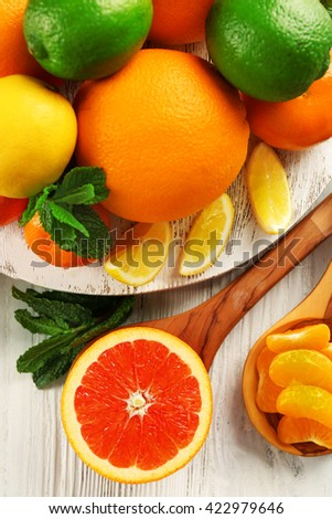 Set of different citrus fruit on light wooden table - stock photo