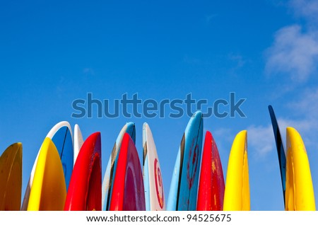 Set of different color surf boards in a stack by ocean - stock photo