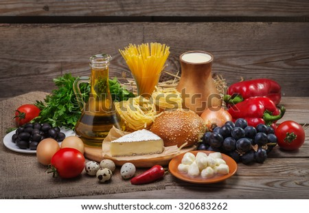 Set of different foods on the old wooden background, vegetables, pasta, fruit, eggs, dairy products, the concept of a balanced diet, the ingredients for Italian food - stock photo