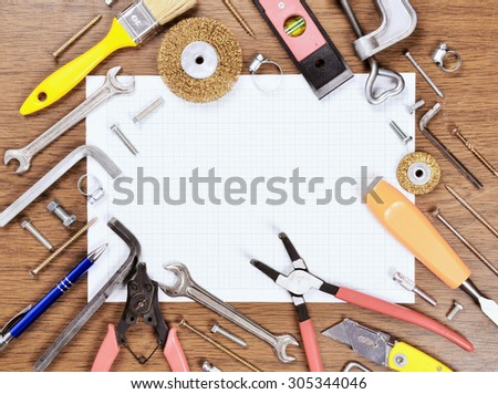 Set of different old Tools and grid paper on wooden background - stock photo