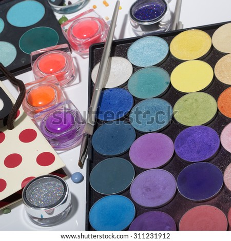 Set of different professional eyeshadow palette red orange green violet pink yellow purple black beige brown colors foundation powder and make-up brushes on white background, square picture - stock photo