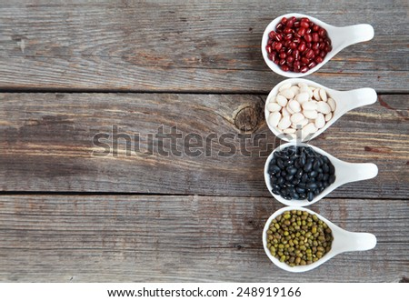 Set of different varieties of beans: baby lima, black small, adzuki and  mung in white ceramic spoons (appetizers) on wooden background, selective focus on beans