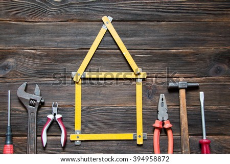 Set of different work tools are in the form of a house: screwdriver, hammer, hand saw, meter, wrench over dark wooden background. House concept. Build a house. Repairs. - stock photo