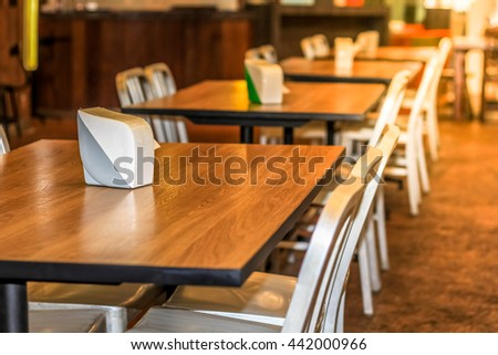 Set of dining table, Wood table top and white chairs in the hotel restaurant , decorate with warm light
