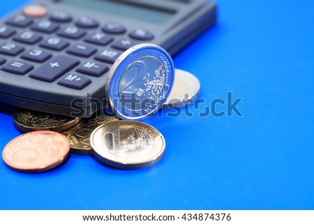 Set of European coins near calculator on blue background