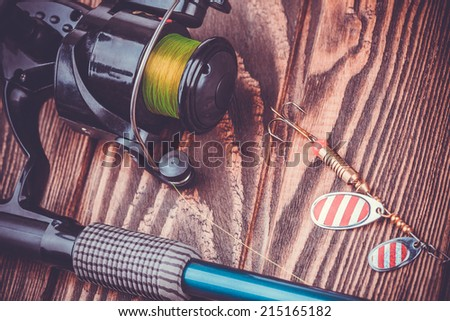 set of fishing tackle on a wooden table - stock photo