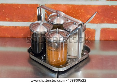 Set of Food Seasoning in glasses, Cayenne Pepper, Fish Sauce, Sugar and Vinegar, with aluminum tea spoon in front of brick as background - stock photo