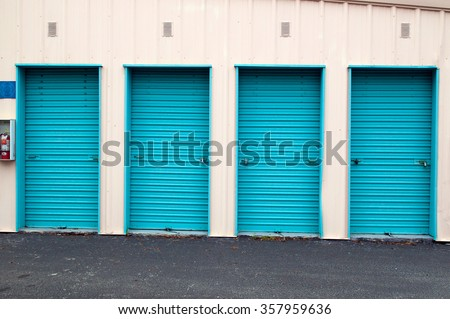 set of four metal roll up doors of storage units, closed and locked.