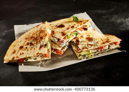Set of four nutrious cooked chicken wheat tortilla quesadillas stuffed with onion, tomato and herbs in wax paper on dark table - stock photo