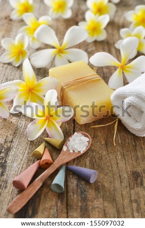 set of frangipani ,towel, oil, salt in spoon ,soap on old wood background  - stock photo