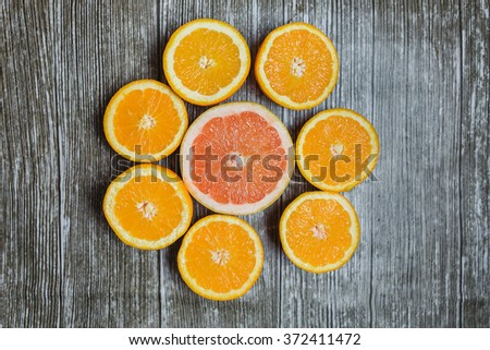 Set of fresh sliced citrus fruits: orange, grapefruit  over wooden background. Top view. - stock photo