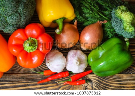 Set of fresh vegetables. Ingredients for a delicious vegetarian dish. Broccoli, pepper, garlic, dill, onion on wooden background. Top view.