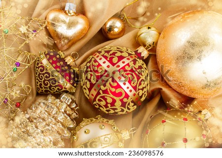 set of golden christmas balls decoration on soft silk background with sparkles