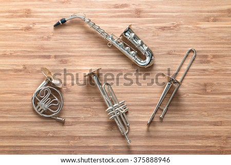 Set of golden toy brass wind orchestra instruments: saxophone, trumpet, french horn, trombone. Music concept. - stock photo