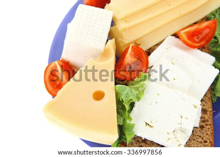 set of gourment cheese slice and chunk ( bar)  white goat greek yellow french aged on half of rye bread on green lettuce salad with tomatoes on blue plate isolated over white background - stock photo