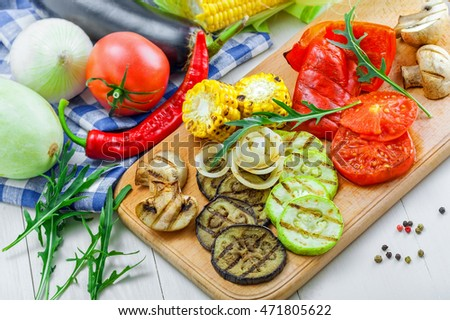 Set of grilled vegetables meal and ingredients: tomato, corn, eggplant, mushroom, bell pepper, marrow and onion. Healthy organic food on a table.