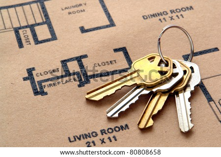 Set of house keys on a key ring over real estate home construction builder architectural floor plan printed on brown recycled paper - stock photo